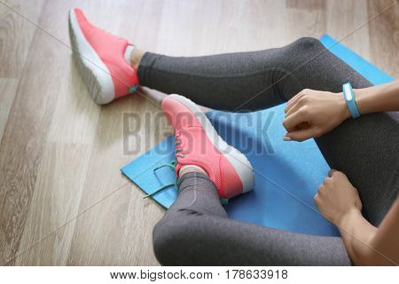 Young woman with fitness tracker sitting on floor in gym