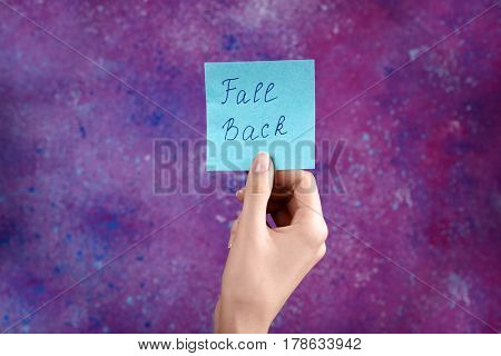 Female hand holding card with text FALL BACK on color background