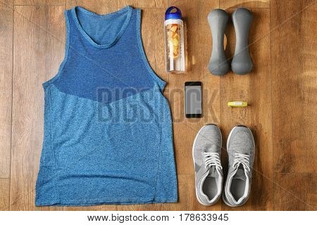 Fitness tracker and sports clothing with dumbbells on wooden floor, top view