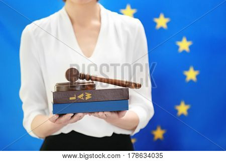 Woman holding judge gavel and law books on European Union flag background