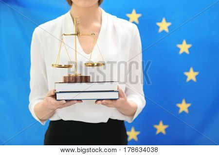 Woman holding scales and law books on European Union flag background