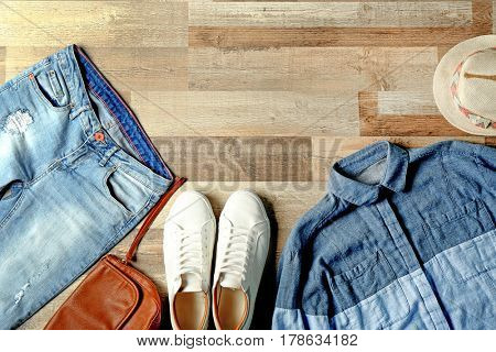 Set of stylish clothes and accessories on wooden background