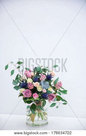 Glass vase with beautiful bouquet on light background