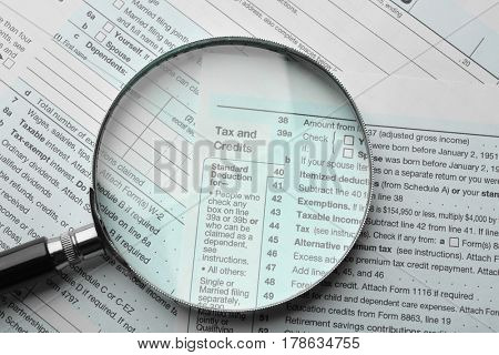 Income tax return form with magnifying glass