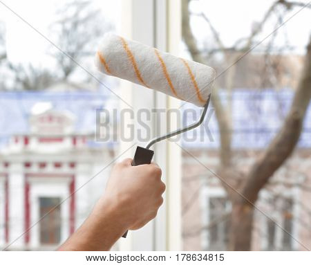Hand of young man going to paint window in office