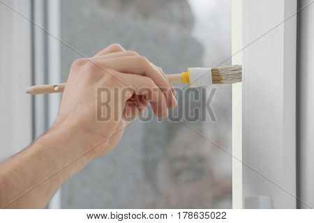 Hand of young worker painting window in office