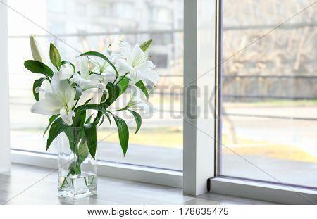 Vase with beautiful white lilies on windowsill