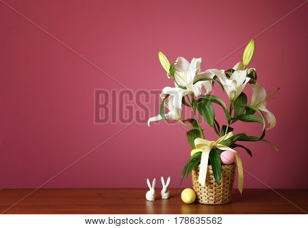 Beautiful composition with white lilies and Easter decor on color background