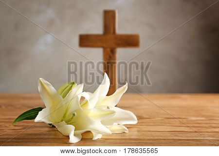 White lily and wooden cross on table
