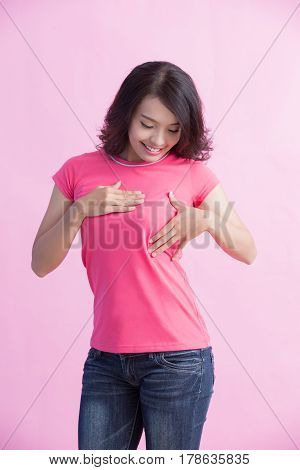Happy woman check her chest with pink ribbon great for prevention breast cancer concept