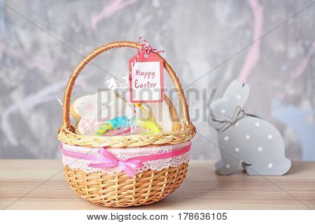 Easter basket with sweets, toy and greeting card on blurred background