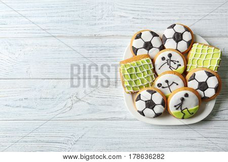 Plate with creative cookies decorated in football style on wooden background