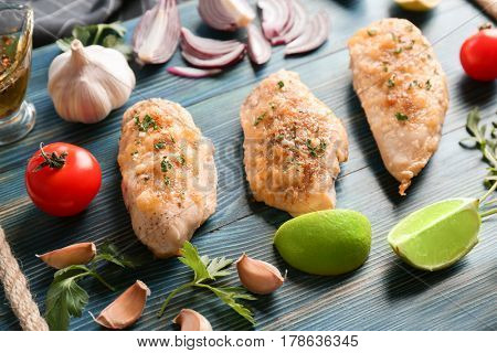 Tasty chicken breasts with vegetables on wooden board