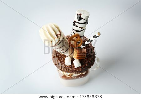 Milkshake, donut and other sweets in jar on white background