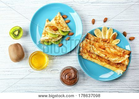 Delicious pancakes with fruits on wooden table