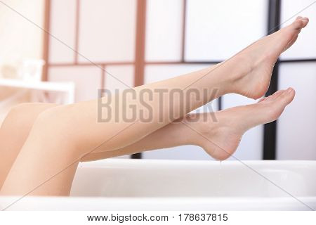 Legs of beautiful young woman taking bath at home