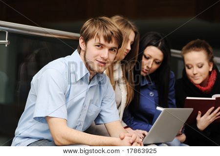 Young group of students with laptop and books working together