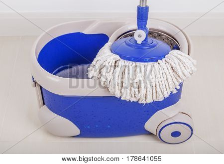 Close Up Of Mop And Blue Bucket For Cleaning Floor