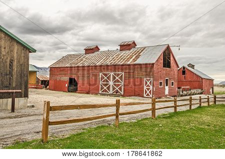 Corrugated metal roofs with rust and weathered wood on the barn blend together on the red barn with white trim