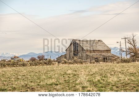 Old barn with a roof that looks like lattice with wavy lines and a beautiful mountain background