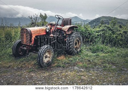 An old tractor parked at the roadside in the mountains after rain