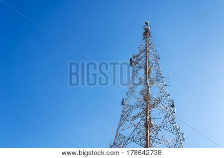 Telecommunication tower for used to transmit telephone or television signal with blue sky.