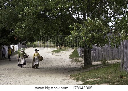 Plimoth Plantation, Plymouth, Massachusetts - September 10, 2014 - Wide view of two pilgrim women walking up a path woven baskets in hand at Plimoth Plantation surrounded by trees and foliage on a bright sunny day in September.