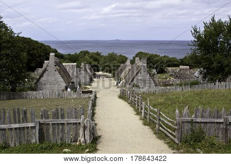 Plimoth Plantation, Plymouth, Massachusetts - September 10, 2014 - Wide shot of a path leading through the Pilgrim Village at Plimoth Plantation, Plymouth, Massachusetts with tourists walking among the old thatched cottages with Cape Cod Bay on a bright s