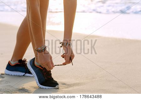 Healthy runner woman tying running shoes laces getting ready for beach jogging. Female athlete living a fit and active life