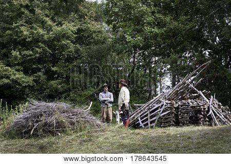 Plimoth Plantation, Plymouth, Massachusetts - September 10, 2014 - Wide view of two pilgrims taking a break and talking beside a large wood pile on a small hill at Plimoth Plantation Massachusetts with trees and foliage on a bright sunny day in September.