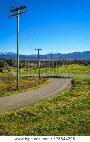 Country road leading to a cattle farm on winter season. Asphalt road to a valley in British Columbia. Rural road with power posts on the side and mountain view background