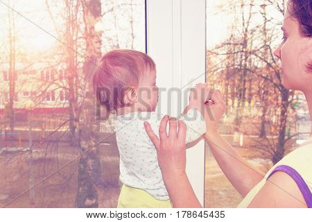 Mom with a child near the window. Mom and little baby girl close the window with a key. Child safety. You can not fall out of the window. Drop out of the window. Carefully follow the child near the window.