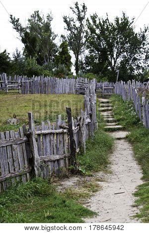 Vertical of a small old wood fenced path leading through the old Pilgrim's Settlement at Plimoth Plantation, Plymouth, Massachusetts surrounded by trees and foliage on an overcast but bright day in September.