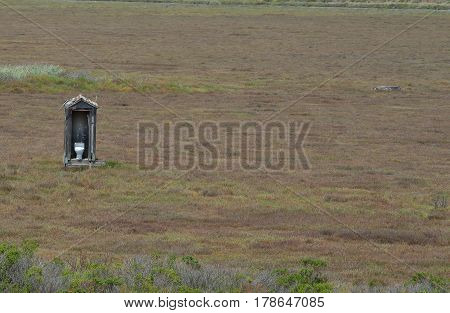 White toilet in outhouse out in open field