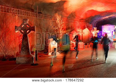 STOCKHOLM SWEDEN - MAR 25 2017: Tunnel with red light tomb stones and running people looking like ghosts the Stockholm Tunnel Run Citybanan 2017. March 25 2017 in Stockholm Sweden