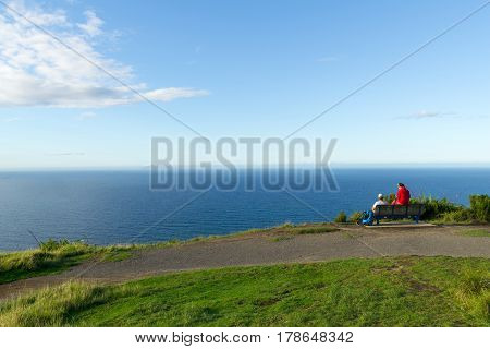 Mount Maunganui, New Zealand - March 27, 2017; Couple sitting near summit Mount Maunganui, taking a break and looking at the sea view.