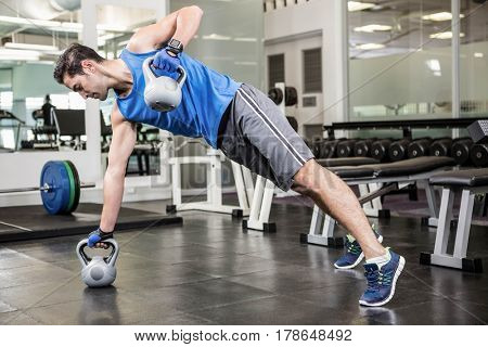 Muscular man doing exercises with kettlebells at the gym