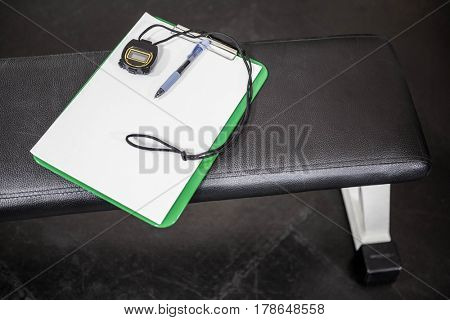 Clipboard and stopwatch on a bench in the gym