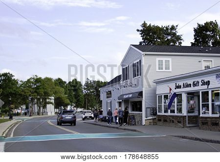 Plymouth, Massachusetts - September 11, 2014 - Wide view of the main street in Plymouth, Massachusetts with people stores landmarks and foliage on a bright sunny day with blue skies and clouds in September.