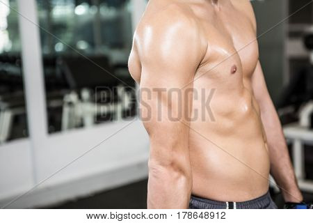 Shirtless muscular man showing arm in the gym