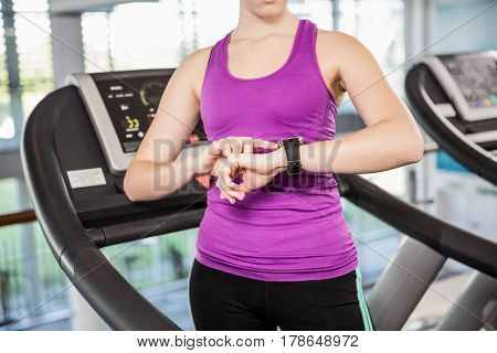 Mid section of fit woman using smartwatch on treadmill at the gym