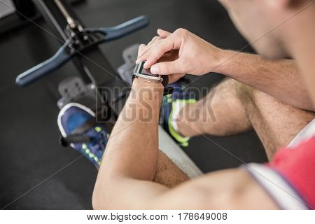 Muscular man on rowing machine using smart watch in the gym