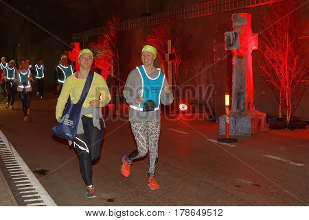 STOCKHOLM SWEDEN - MAR 25 2017: Smiling girls running in a tunnel with red light the Stockholm Tunnel Run Citybanan 2017. March 25 2017 in Stockholm Sweden