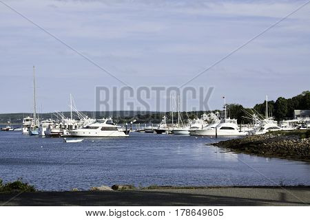 Wide shot boats and yachts in Plymouth Harbor with shoreline and foliage in Plymouth, Massachusetts on a bright sunny day with blue skies and clouds in September.
