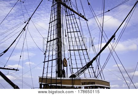 Wide view of the rigging main mast and the top of the main cabin of a tall ship slightly skewed for effect against a beautiful blue sky and clouds in Plymouth Harbor, Plymouth, Massachusetts on a bright sunny day in September.