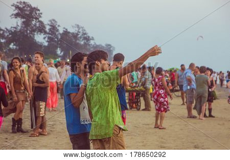 ARAMBOL BEACH GOA INDIA - FEBRUARY 23 2017: Two indian man are taking photo on mobile on Arambol beach at sunset in Goa India on February 23 2017.