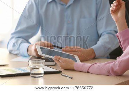 Young managers with tablet computer discussing issues in office, closeup