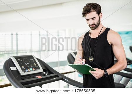 Serious trainer writing on clipboard at the gym