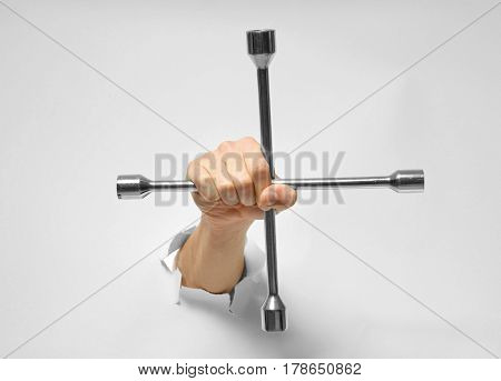 Hand of auto mechanic with wheel wrench tearing white paper background