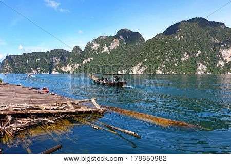 Khaosok or Ratchaprapa Dam in Southern of Thailand. The mountain and blue sky in background with bamboo raft and a tourist boat in the clear water. This photo took in July 2016.